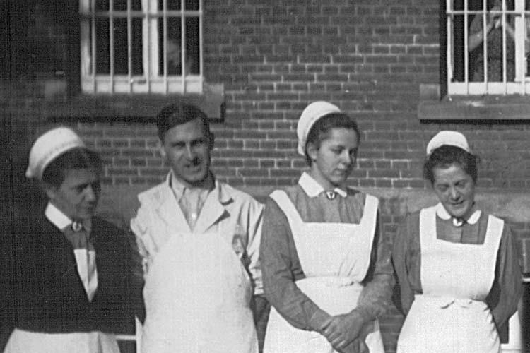 Krankenschwestern und ein Pfleger der Heil- und Pflegeanstalt Wehnen vor dem Hauptgebäude der Klinik um 1943. Im Hintergrund Patienten hinter vergitterten Fenstern.