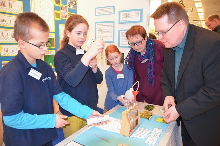 Daniel Langwost, Ida Krause und Charlotta Kruse erklären im Beisein ihrer Lehrerin Birgit Krah einem Besucher ihre Experimente.
